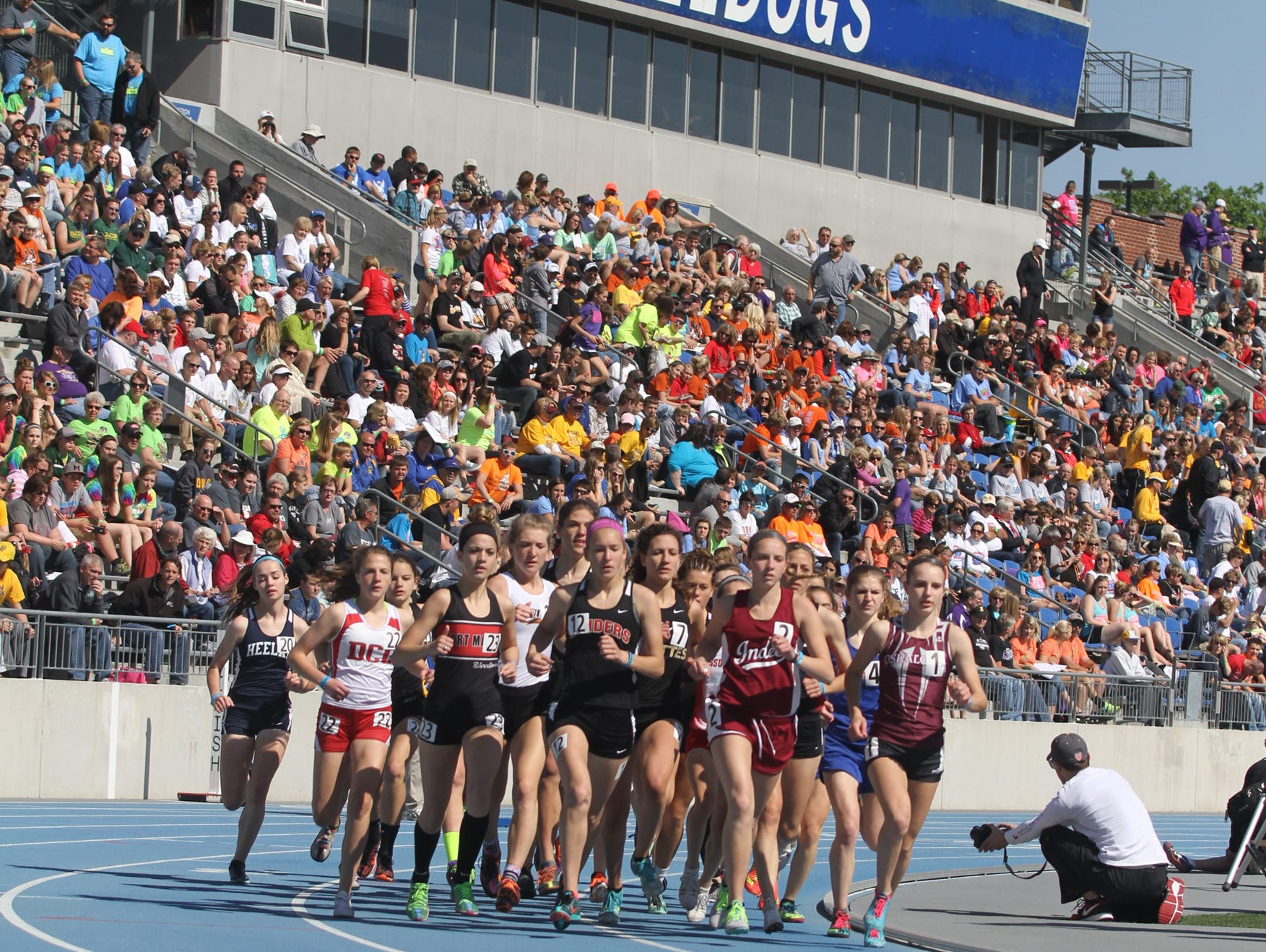 Williamsburg junior Julie Hollensbe (12) and the rest of the pack in the Class 3-A 3,000-meter run pass the grandstand at Drake Stadium Thursday during the state track meet.