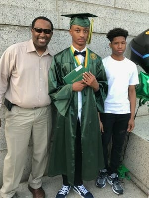 """Louis Steptoe, 18, is shown as his recent high school graduation with his godfather William Ford and Ford's son, Jabari Ford, who Steptoe calls his """"godbrother."""""""