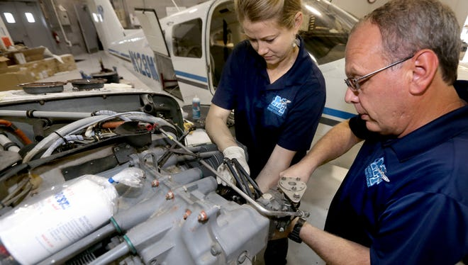 Doris Gossett, an aircraft mechanic, left and Matt Taylor aircraft maintenance manager, right work together to remove a cylinder from a Piper Seminole, at the Murfreesboro Airport on Friday Aug. 14, 2015.