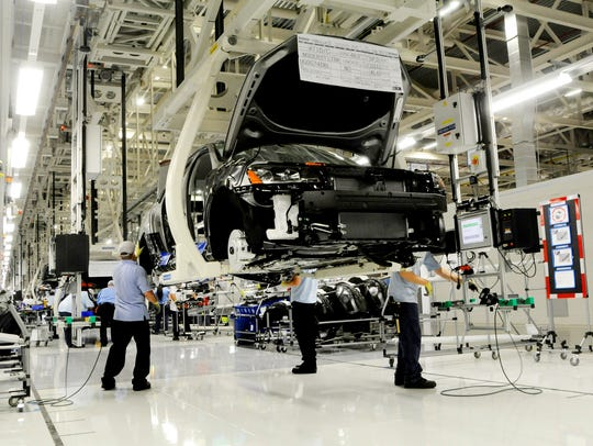 Workers inspect the undercarriage of a new Passat inside