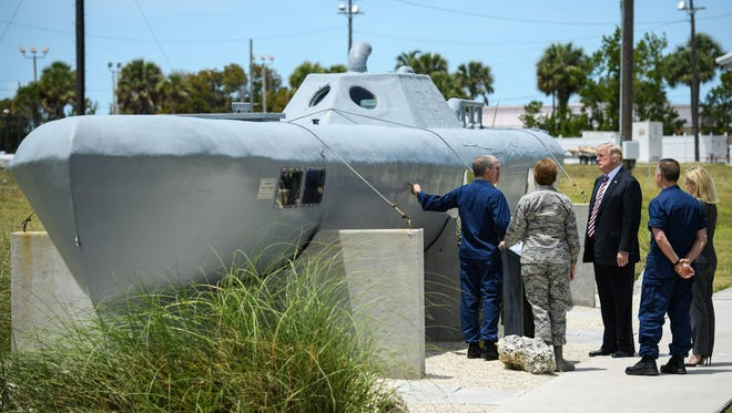 President Trump receives a briefing on a semi-submersible used by drug smugglers during a visit to Joint Interagency Task Force South at Naval Air Station in Key West, Fla.