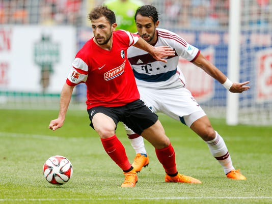 Freiburg's Admir Mehmedi from Switzerland. left, and Bayern's Xabi Alonso challenge for the ball during a German first division Bundesliga soccer match between SC Freiburg and Bayern Munich in Freiburg, Germany, Saturday, May 16, 2015. (AP Photo/Michael Probst)