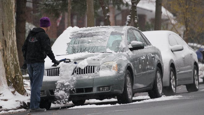 A motorist removes snow off his vehicle along Delaware Avenue in Trolly Square on Tuesday afternoon.