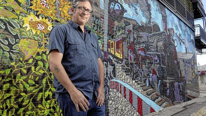 Artist Curtis Goldstein stands June 18 next to the mural he created on the wall of Otie's Tavern & Grill as the first public art piece commissioned by the Hilliard Public Arts Commission. The artwork represents the city's railroad heritage.