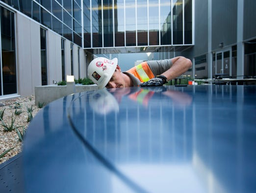 Shaffer Pulen, a contract worker, installs benches at the new tower at Banner Estrella Hospital, in Phoenix, Az.