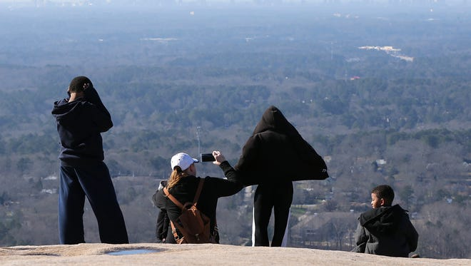 """Participants pause to take in the view of the Atlanta skyline as they near the summit while commemorating the life of Dr. Martin Luther King, Jr., by climbing to the top of Stone Mountain with children who aspire to be great during """"The Dream Walk"""" in Stone Mountain Ga. In his """"I Have A Dream"""" speech, Dr. King spoke of a symbolic bell of freedom ringing from the tops of Stone Mountain to the hills of Tennessee."""