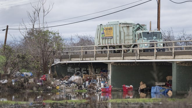 More than half a dozen shopping carts, some partially submerged in water, surrounded by building materials, tarps, furniture, a bicycle and other debris are gathered around the Ben Maddox Way bridge over the St. Johns River on Wednesday.