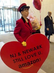 "In this Feb. 14, 2019 photo provided by Newark Alliance, Laurie Ross, an actor with the event planners at Life 'O the Party, holds a message reading ""NJ & Newark Still Love U, Amazon!"" while arriving at an Amazon office in New York. The love note came despite Amazon saying it's not seeking a new site."