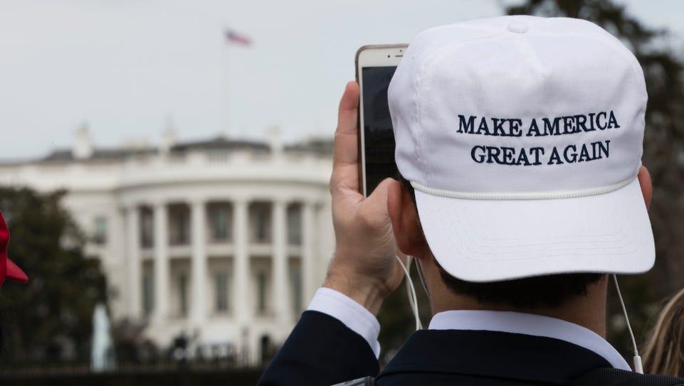 A man photographs the White House in Washington Thursday