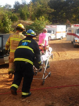 Firefighters move a training mannequin from the simulated crash scene to an awaiting ambulance.