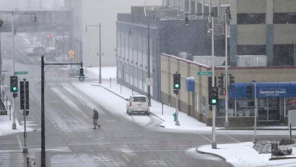 Snow begins to accumulate as a pedestrian crosses Washington Street Tuesday, April 3, 2018, in Appleton, Wis.