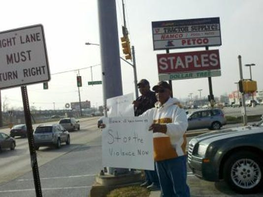 This file photo by Kara Eberle shows Jerome Carter, 72, and his brother, Bennie Carter, 76, standing along Route 30 in York holding signs that urge drivers to honk if they want to stop the violence.