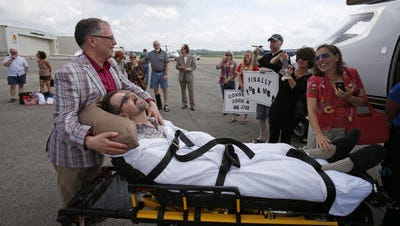 Jim Obergefell, front left, and John Arthur of Over-the-Rhine, are surrounded by well-wishers after returning from their wedding flight at Landmark Aviation at Cincinnati's Lunken Airport Thursday July 11, 2013.