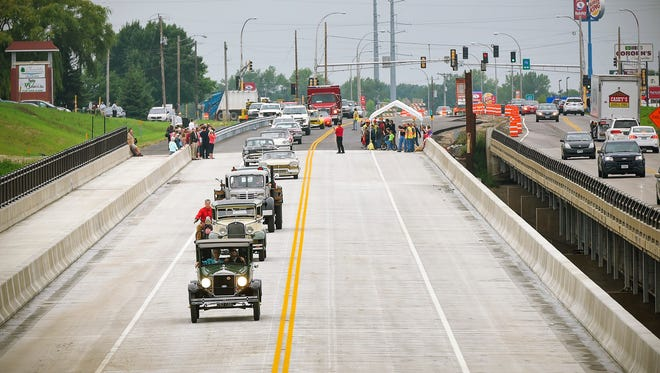 A procession of antique and custom vehicles followed by a firetruck made the ceremonial first crossing of the new Minnesota Highway 24 bridge over the Mississippi River Wednesday, Aug. 16, in Clearwater.