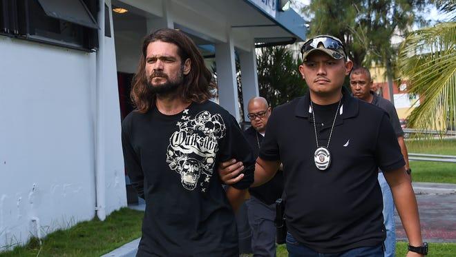 Robert Isaac Revels is escorted from the Guam Police Department Hagåtña Precinct on Dec. 15, 2017.