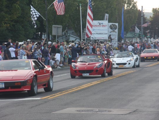 Spectators are thrilled as sports cars drive along