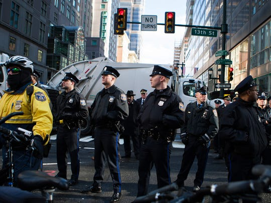 Philadelphia police officers stand near the barrier on 13th and Market streets where protesters stop and gather to protest President Donald Trump who meets with GOP delegation in Center City Philadelphia.