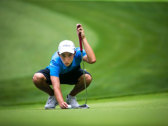 Danny Dougherty checks his line on the putting green of the 13th hole in the final round of the DSGA Junior Boys golf tournament at Deerfield Golf Course.