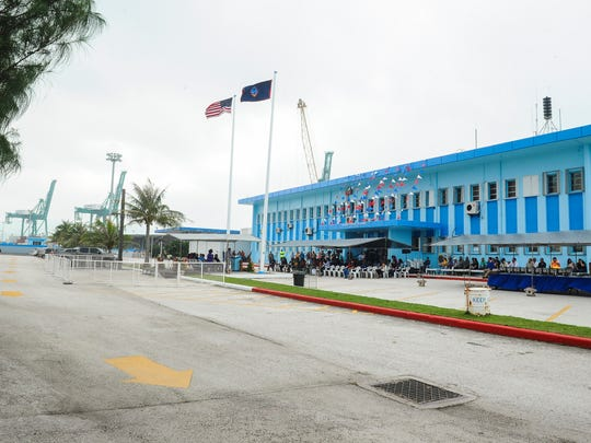 The American and Guam flags fly in a brisk breeze during a flag raising ceremony at the Jose D. Leon Guerrero Commercial Port in Piti in October 2015.