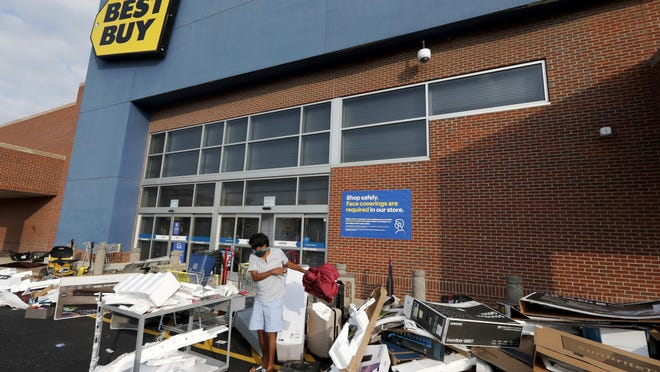 Volunteers help clean up the parking lot outside a Best Buy store, Monday, Aug. 10, 2020, after vandals struck overnight in the Lincoln Park neighborhood in Chicago. Chicago's police commissioner says more than 100 people were arrested following a night of looting and unrest that left several officers injured and caused damage in the city's upscale Magnificent Mile shopping district and other parts of the city.