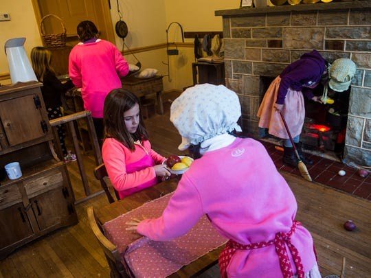 Haylie Kump, 8, of Gettysburg, center, helps arrange a table at in the General Store room with other children at Explore & More in Gettysburg.  It's one of the places in the region that families can go when it's cold.