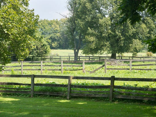 Looking across fenced horse pastures at the former Blakey property from the back of the main stone house. Horses were part the property for the past 45 years.