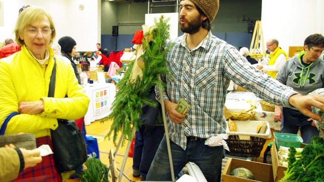 One vendor at the Brighton Winter Farmers Market, Denis Lepel of Lakestone Family Farm in Farmington, right, started planning for this winter's sales a year ago.