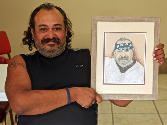 Marco Castillo holds his portrait during an event at Our Lady of Solitude Church in Palm Springs on Thursday, Nov. 19, 2015. Local artist Martha Inglis created a series of portraits depicting clients of Well in the Desert, a non-profit organization that assist the less fortunate in the Coachella Valley.