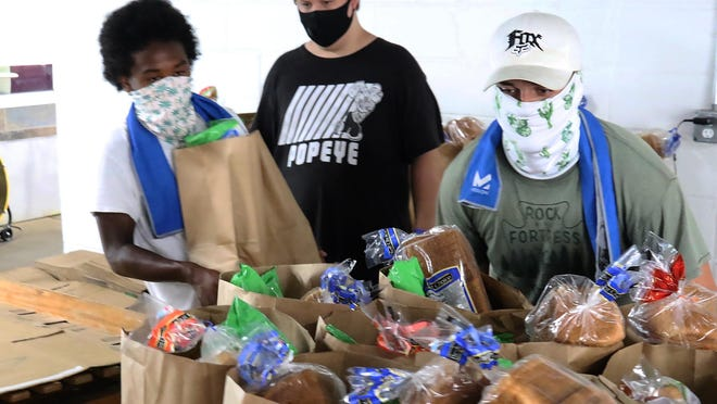 """Volunteers Joaquin Fox, from left, Haydden Dalton, and Micah Fox, set out bags of groceries for pick-up, Friday, July 24, 2020, at the Antioch for Youth & Family """"Veterans Only,"""" drive-thru food distribution at the Antioch facility, 1420 N. 32nd St."""