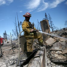 A firefighter waters down hot spots in Weed.