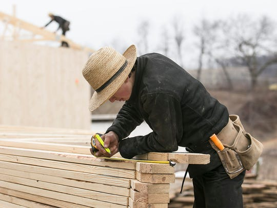 A young amish teenager, who chose not to be identified, measures out a truss edge Thursday, March 3, 2016, in Codorus Township. The Amish are expanding west of Lancaster because of the lack of farmland there. Amanda J. Cain photo