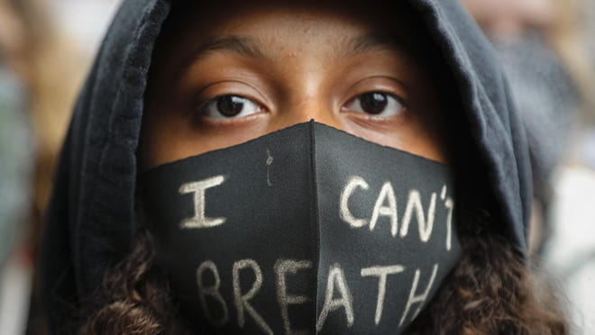 A girl wears a face mask during a Black Lives Matter rally in Parliament Square, in London, Saturday, June 6, 2020, as they protest against the killing of George Floyd by police officers in Minneapolis, USA. Just like the coronavirus, racism has no borders. Across the world, disgruntled people, representing a broad spectrum of society, marched this weekend as one to protest against racial injustices at home and abroad.