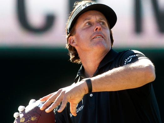 Feb. 1, 2014 - Phil Mickelson tosses autographed footballs into the crowd at the 16th hole during the third round of the Waste Management Phoenix Open at the TPC Scottsdale.