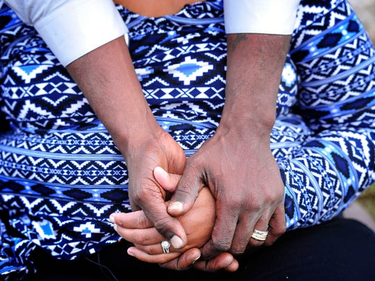 Johnny Footman holds the hand of his wife, Tiffany,