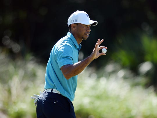 In a file photo from 2015, Tiger Woods shows his ball