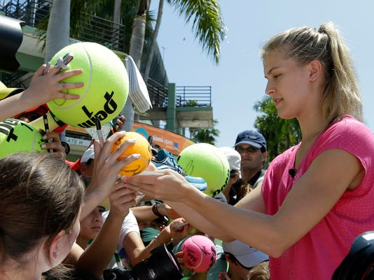FILE - In this March 24, 2015, file photo, Genie Bouchard, of Canada, signs autographs at the Miami Open tennis tournament in Key Biscayne, Fla. Bouchard may have to go on a date with a fan in order to make good on a Twitter bet made during the Super Bowl on Feb. 5, 2017. (AP Photo/Lynne Sladky, File)