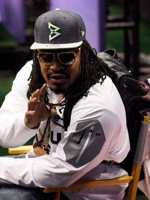 Seahawks running back Marshawn Lynch sits at his podium during media day for Super Bowl XLIX at US Airways Center.