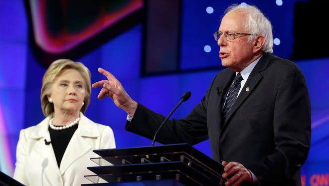 Democratic presidential candidate Sen. Bernie Sanders, I-V.t, right, speaks as Hillary Clinton listens during the CNN Democratic Presidential Primary Debate at the Brooklyn Navy Yard in New York on April 14, 2016.