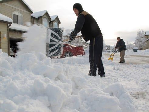 Gregg Schneider, left, and Mathew Cornett, right, clear snow from their driveways in Bellemont, Ariz., on Dec. 20, 2013.