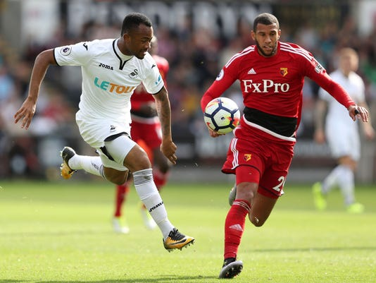 Swansea City's Jordan Ayew, left, and Watford's Etienne Capoue battle for the ball during their English Premier League soccer match at the Liberty Stadium, Swansea, Wales, Saturday, Sept. 23, 2017. (David Davies/PA via AP)