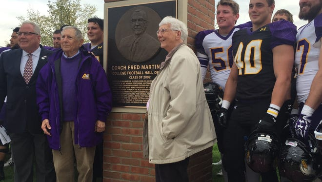 Fred and Ruth Martinelli are flanked by Ashland University Gridiron Club president Don Graham and members of the football team at Saturday's ceremonial unveiling of pillars to Martinelli and fellow College Football Hall of Famer Bill Royce, one of his players.