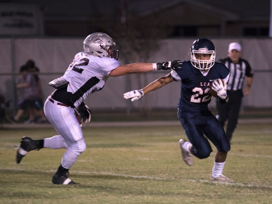 LCA running back Trey Breaux runs the ball past an Eagle defender with time winding down in the first half.
