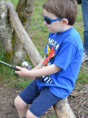 Avery Puhn of Eugene makes an angling fashion statement during a recent Family Fishing Event at St. Louis Ponds.
