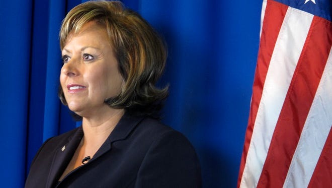 In this Oct. 6, 2014 photo, New Mexico Gov. Susana Martinez, a Republican and the nation's only Latina governor, stands next to an American flag before participating in a Spanish-language television debate in Albuquerque, N.M. with a Democratic opponent who she later defeated.