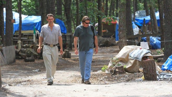 Steve Brigham, founder of Tent City (left), walks with filmmaker Jack Ballo in July 2013.