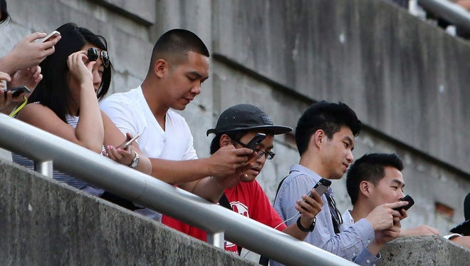People use their phones in Toronto, Monday, July 18, 2016.