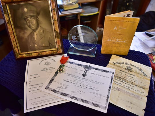 Military discharge papers, an old service photo, a French Legion of Honor medal and other military memorabilia of Austin Powlis, a 92 years old decorated WWII vet who was part of the famous Red Ball Express, in Teaneck, on Tuesday, February 14.