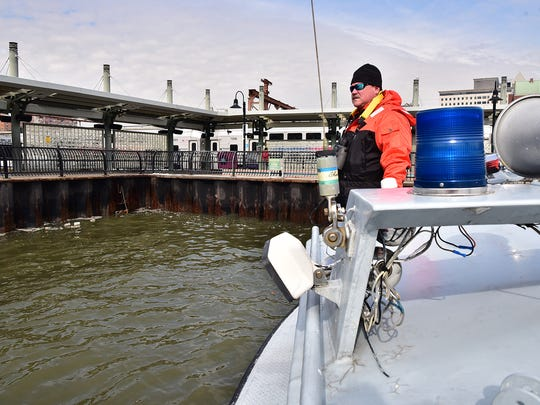 Paull scans for unauthorized discharge at a sewage outflow near the Hoboken Terminal during a patrol on Feb. 15.