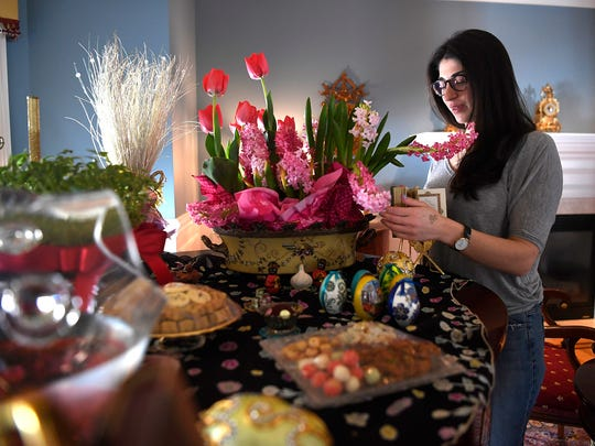 Marjan Ebrahimi adjusts the flowers on the haft-seen, the display for the Iranian new year, or Nowruz, in her home in Mahwah, New Jersey, in 2017.