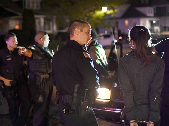 Haledon police officers question people under arrest for alleged possession of marijuana during a traffic stop.